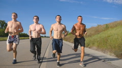 Group of runners men jogging at highway. Male sport athletes training outdoor Stock Footage