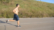 Young strong man running on road in beautiful nature. Male runner jogging Stock Footage
