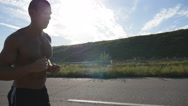 Male runner jogging during workout training on country road at sunset. Slowmo Stock Footage