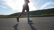 Young strong man running on road in beautiful nature. Slow Motion Stock Footage
