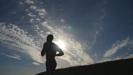 Silhouette of man jogging in the country at sunset time.  Slow motion Stock Footage