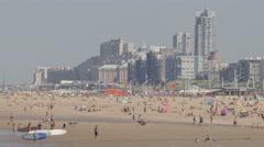 Tourists on beach with beachside hotels,Scheveningen,Netherlands Stock Footage