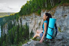Young woman with backpack sitting on cliff's edge at high mountain Stock Photos