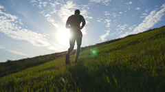 Young man running over green hill over blue sky background. Slow motion Stock Footage