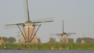 3 Windmills in line along river with reed,Rottemeren,Netherlands Stock Footage