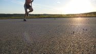 Male runner jogging during workout training on country road at sunset Stock Footage