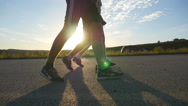 Male feet is walking on a rural road at sunset, slow motion, close-up Stock Footage