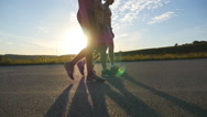 Three men is walking down an empty country road. Guy crossing a sunlit route Stock Footage