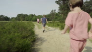 Children running after parents Stock Footage
