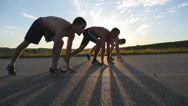 Three young muscular men at the sprint start.  Slow motion. Stock Footage