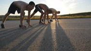 Group of athletes are crouching at starting line before a race and running Stock Footage