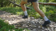 Feet of athletes running at the forest path in autumn. Close-up, slow motion Stock Footage