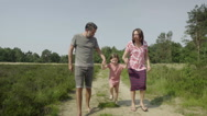 Girl walking with parents Stock Footage