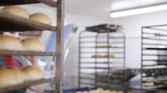 4K Worker in bakery kitchen talking on phone as she checks trays of bread Stock Footage