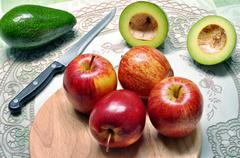 Fruits of avocado and apple on the cutting board Stock Photos