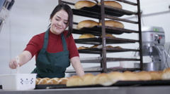 4K Happy young worker in bakery kitchen brushing glaze onto buns Stock Footage