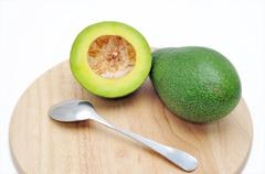Avocado on the cutting board with spoon in a white background Stock Photos