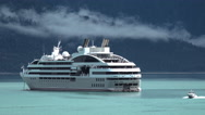 Cruise Ship Sitting in Emerald Water As Boat Passes Stock Footage