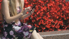 Young girl holds a cellphone and reads messages Stock Footage