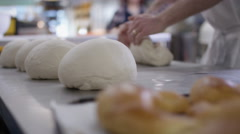 4K Close up on hands of man kneading dough in a bakery shop kitchen Stock Footage