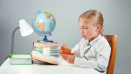 School girl 7-8 years reading book eating muffin sitting at the table Stock Footage