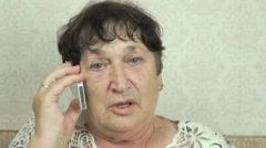 Elderly woman talking on the phone at home Stock Footage