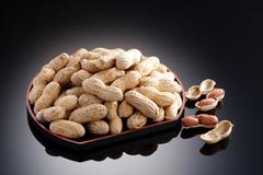 Dried salted peanuts on black plate in restaurant Stock Photos