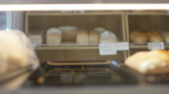 4K Smiling bakery worker putting pastries onto shelves in display cabinet Stock Footage