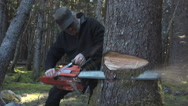 Man in Black With Powerful Chainsaw and Flying Debris Stock Footage