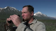 Man in Mountain Setting Scanning Distance With Binoculars Stock Footage