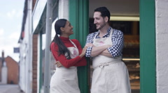 4K Happy couple - small business owners standing together outside bakery shop Stock Footage