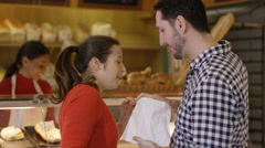 4K Playful couple in bakery shop feeding each other cake Stock Footage