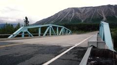 Modern Family Vehicle Passing past Camera Steel Bridge Mountain Scene Stock Footage