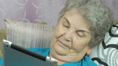 Old woman relaxes using a tablet computer Stock Footage