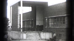 1939: two adult men working labor job during the daytime near a building  Stock Footage