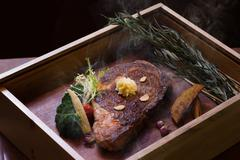 Roast smoked Angus eye steak on wooden box in black background Stock Photos