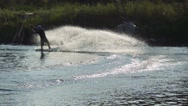 Wakeboarder rides a wakeboard, raising splashes at sunset, slow motion Stock Footage
