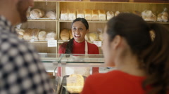 4K Couple in a bakery shop making contactless payment by cell phone Stock Footage