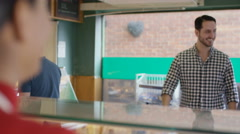 4K Couple in a bakery shop being served at the counter Stock Footage