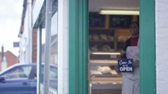 4K Happy Bakery owner holds up a sign to show she is open for business Stock Footage