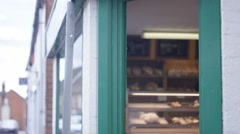 4K Happy Bakery owner holds up a sign to show he is open for business Stock Footage