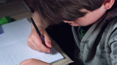 4k Authentic Shot of a Child Doing his Homework, from above Stock Footage