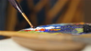 Shallow DOF: Paint brush dips into the white paint on color palette. Stock Footage