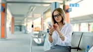 Businesswoman texting on smartphone and smiling to the camera on platform Stock Footage
