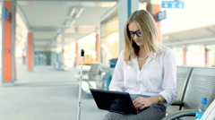 Businesswoman working on laptop while sitting on the train station Stock Footage