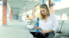 Happy businesswoman chatting on cellphone while sitting on the train station Stock Footage