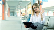 Businesswoman chatting on laptop with someone while sitting on platform Stock Footage