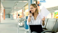 Angry businesswoman talking on cellphone while sitting on the train station Stock Footage
