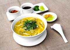 Vietnamese clams porridge in white bowl with lemon and chili sauce Stock Photos