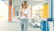 Businesswoman standing on the train station and texting on smartphone Stock Footage